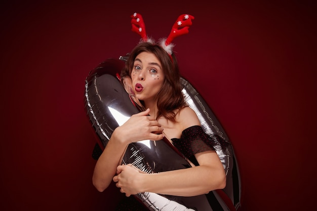 Funny shot of young pretty brunette lady wearing festive makeup while posing, enjoying x-mas theme party and posing with helium balloon