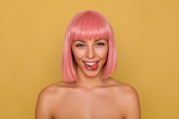 Funny shot of young pretty joyful lady with short pink hair looking playfully at camera and showing her tongue, fooling while posing over mustard background
