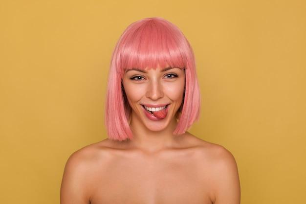 Colpo divertente di giovane signora piuttosto gioiosa con i capelli rosa corti guardando scherzosamente la fotocamera e mostrando la sua lingua, ingannare mentre posa su sfondo senape