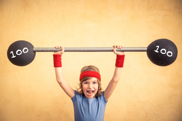Funny shouting child with barbell. girl power and feminism concept. sport fitness success winner kid