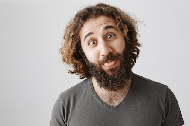 舌を見せて笑っている面白い愚かなひげを生やした中東の男