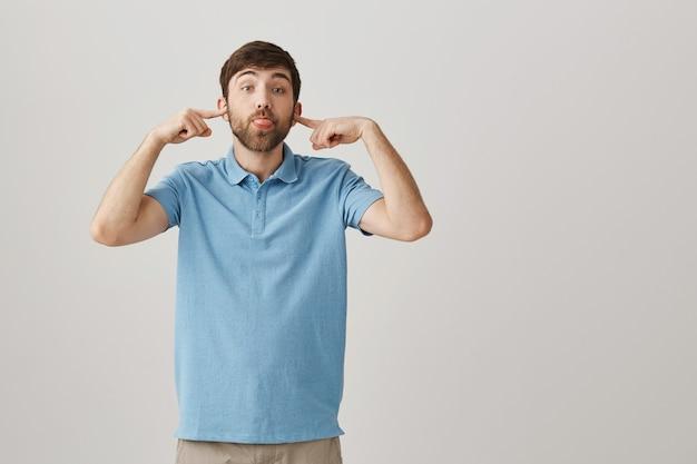 Giovane uomo barbuto divertente e sciocco in posa