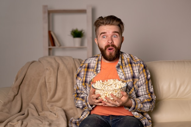 テレビを見ているソファの上の面白い独身男性