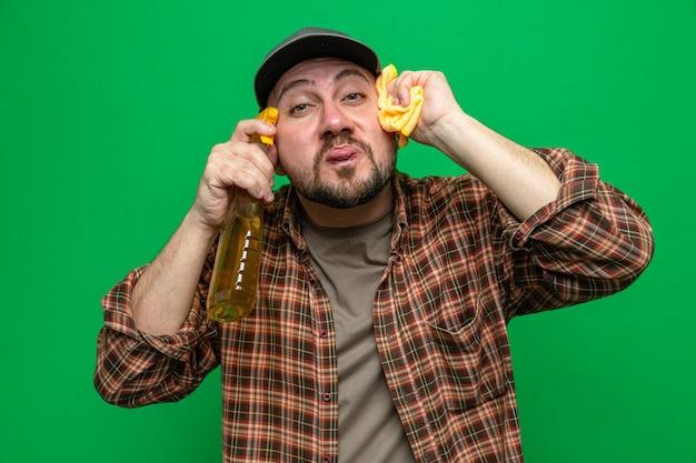 Divertente uomo delle pulizie slavo che si infila la lingua e tiene in mano panni per la pulizia e un detergente spray