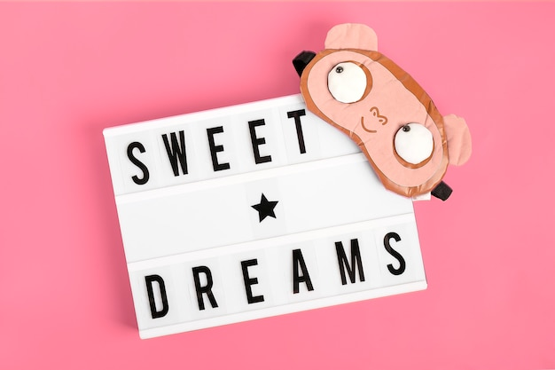 Funny sleep mask and lightbox with  quote sweet dreams on pink background flat lay