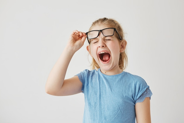 Funny small blonde girl with pretty blue eyes raising glasses and yawning with closed eyes in classroom because long boring lesson.