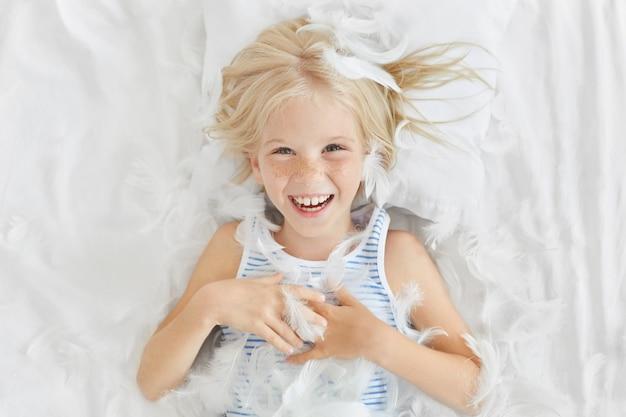 Забавный маленький ребенок со светлыми волосами, лежит на белом постельном белье, испытывает радость, ловя перья, развлекаясь со своими друзьями.