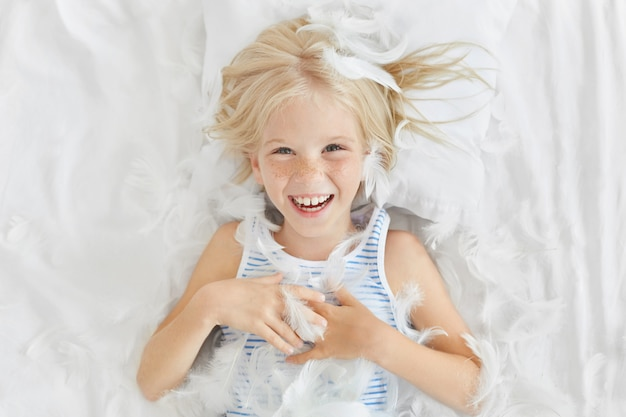 Funny small child with light hair, lying on white bedclothes, feeling joy while catching feathers, having fun with her friends.