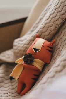 ベージュの背景のかぎ針編みのぬいぐるみの新しいの面白い小さな虎のおもちゃのシンボル