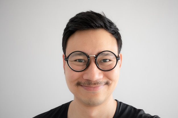 Funny smile face of asian nerd guy with eyeglasses and mustache.