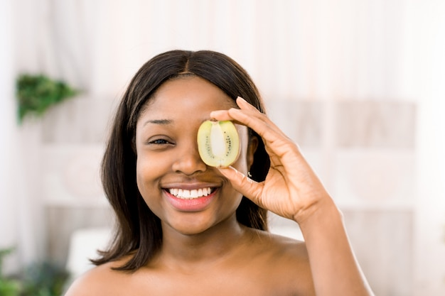 Funny smiling african american young woman holding kiwi half in front of her eye over white background