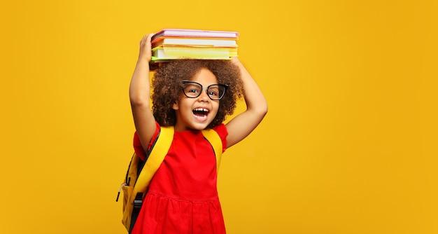 眼鏡をかけた面白い笑顔の黒人の子供の女子高生は、彼女の頭に本を持っています。黄色の背景