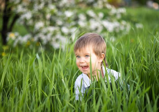 デニムの青いオーバーオールと明るい青い目で面白い笑顔の少年。暖かい春の庭の背の高い緑の芝生に隠れているのは面白いです