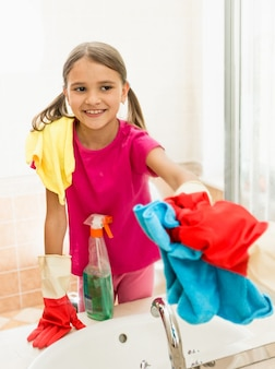 Funny smiling girl polishing mirror at bathroom while cleaning house