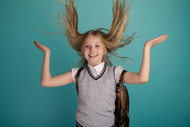 Смешная улыбающаяся девочка поднимает волосы и смеется.