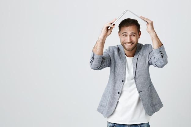 面白い笑顔ハンサムな男は屋根として頭の上にラップトップを保持します