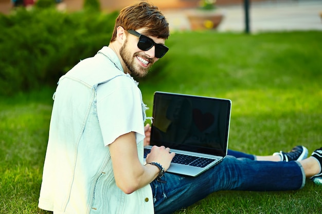 Funny smiling hipster handsome man guy in stylish summer cloth in the street sitting on grass in the park with notebook
