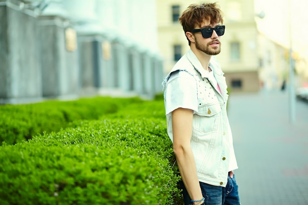 Funny smiling hipster handsome man guy in stylish summer cloth in the street in sunglasses