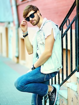 Funny smiling hipster handsome man guy in stylish summer clothes in the street posing near colorful bright wall in sunglasses