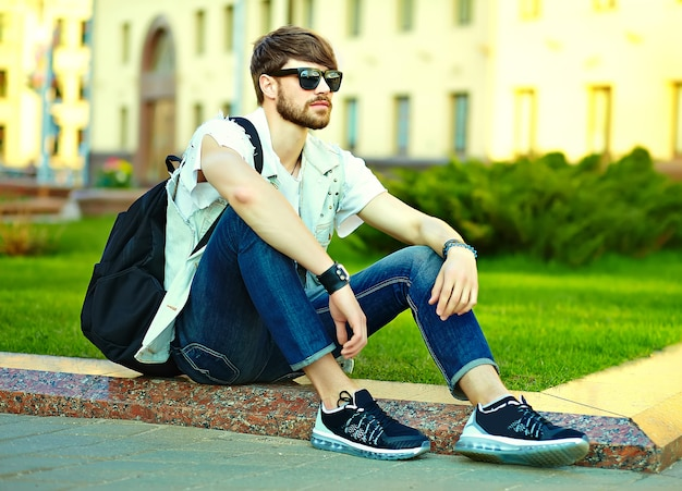 Funny smiling hipster handsome man guy in stylish summer clothes in the street posing sitting on grass in sunglasses