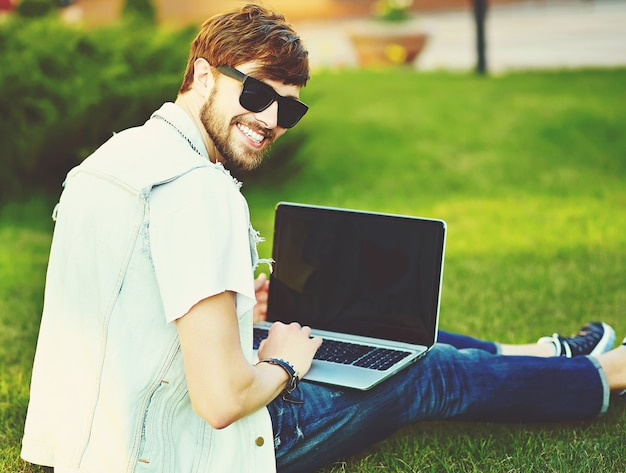 Funny smiling hipster handsome man guy in stylish summer clothes in the street sitting on grass in the park with notebook