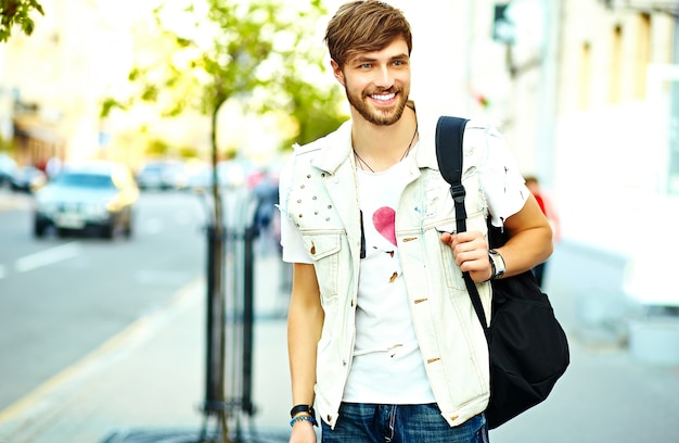 Funny smiling hipster handsome man in stylish summer clothes posing on street background