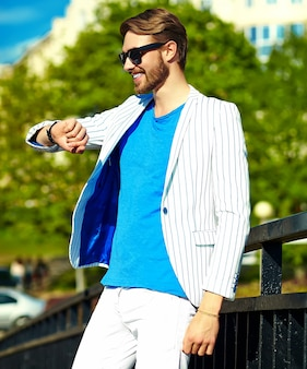 Funny smiling hipster handsome man in stylish summer white suit posing on street in sunglasses, looking at watches