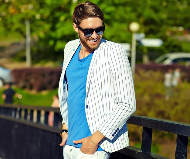 Funny smiling hipster handsome man in stylish summer white suit  posing in street in sunglasses