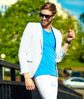 Funny smiling hipster handsome man in stylish summer white suit posing on street in sunglasses