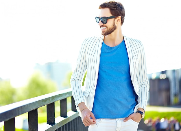 Funny smiling hipster handsome man in stylish summer white suit posing on street wall in sunglasses