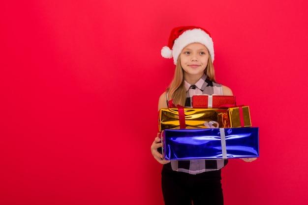 빨간색 배경 위에 손에 크리스마스 선물을 들고 산타 모자에 재미 있은 미소 즐거운 아이 소녀-이미지
