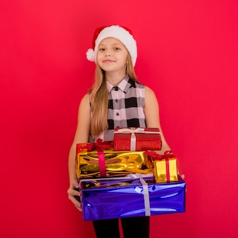 Funny smiling joyful child girl in santa hat holding christmas gift in hand over the red background - image