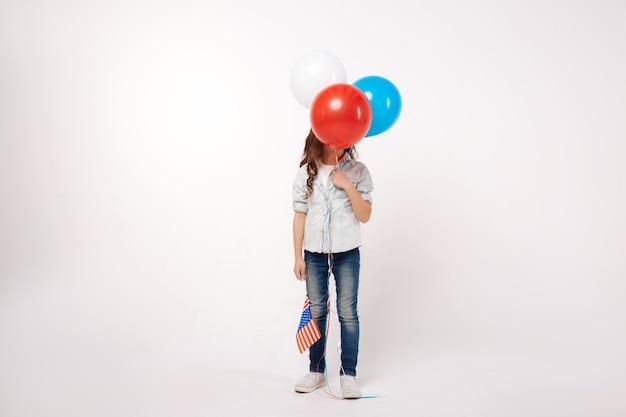 Забавный улыбающийся маленький ребенок, держащий американский флаг и воздушные шары, выражая радость и стоя изолированным на белой стене