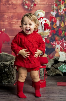 Funny smiling little girl playing in christmas decoration