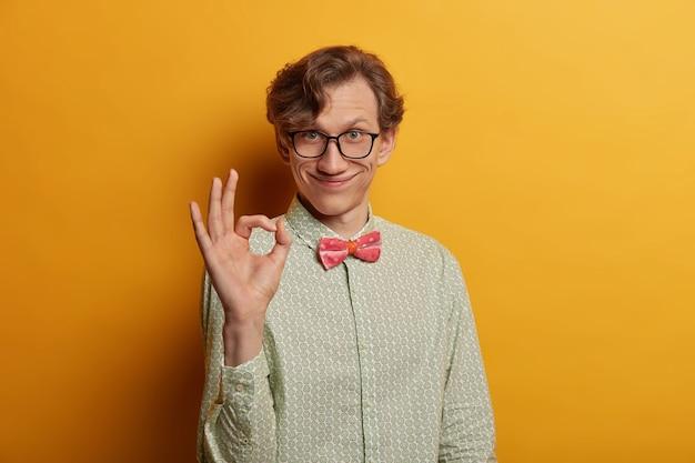웃긴 웃는 남성 괴짜는 손가락으로 반지 제스처를 보여주고, 좋은 직장을 말하고, 제안에 만족하고, 안경과 정장 셔츠를 입고, 기뻐하며, 노란색 벽에 고립 된 모습을 보여줍니다. 무료 사진