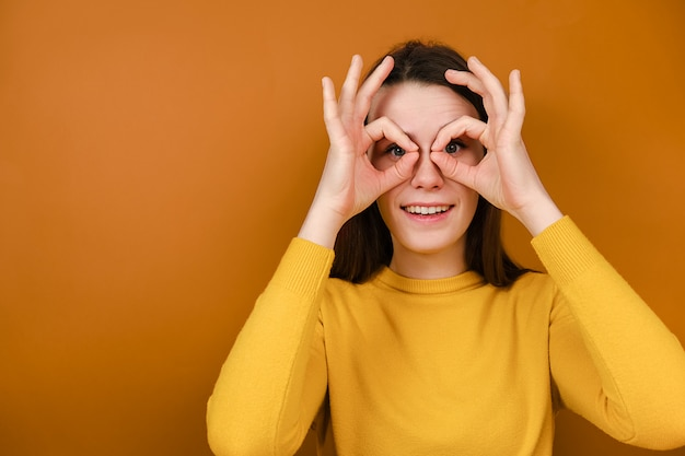 Funny smiling young woman having fun making glasses shape with hands