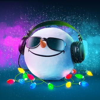 Забавный снежок в наушниках. рождественская вечеринка. музыкальный фон
