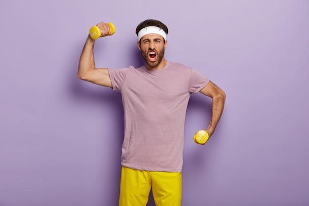 재미있는 운동가는 덤벨로 팔을 들고 감정적으로 외치고 강하고 스포티하며 보라색 티셔츠와 노란색 반바지를 입고 실내에 서 있습니다. 남자는 체육관에서 운동하고 운동을합니다. 보디 빌딩