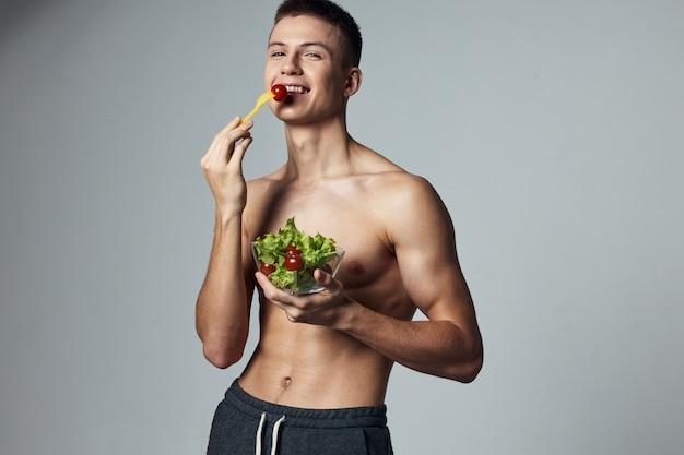 サラダ健康食品の面白いスポーティな男プレートは、トレーニングのビューをトリミングしました。