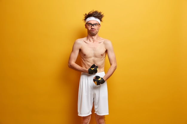 Funny sporty nerd shows biceps or muscles, wears sport gloves and shorts, has serious strict expression, wants to have strong body, doesnt want to be weak, poses against yellow wall