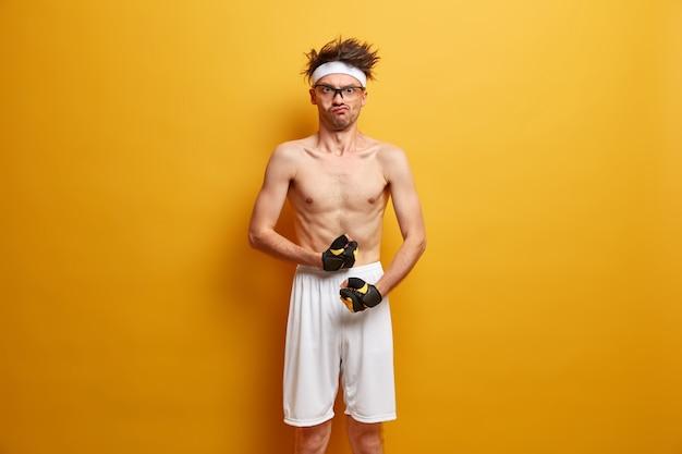 Divertente nerd sportivo mostra bicipiti o muscoli, indossa guanti e pantaloncini sportivi, ha un'espressione seria e rigorosa, vuole avere un corpo forte, non vuole essere debole, posa contro il muro giallo