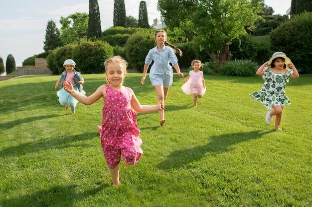 面白いスタート。キッズファッションコンセプト。公園で走っている10代の少年と少女のグループ。子供たちのカラフルな服、ライフスタイル、流行色のコンセプト。
