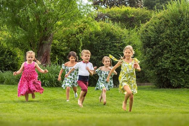 面白いスタート。キッズファッションコンセプト。公園で走っている10代の男の子と女の子のグループ
