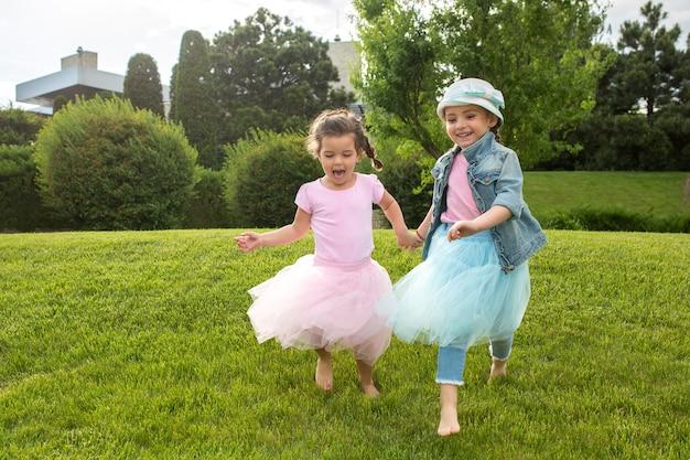 재미있는 시작. 키즈 패션 개념. 공원에서 실행하는 십 대 소녀의 그룹입니다. 어린이 화려한 옷, 라이프 스타일, 유행 색상 개념.