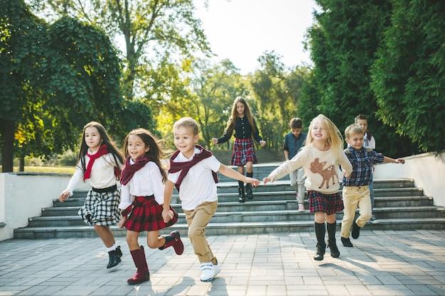 재미있는 시작. 키즈 패션 컨셉입니다. 공원에서 달리는 십대 소년 소녀 그룹. 어린이들은 화려한 옷, 라이프스타일, 트렌디한 색상 개념.