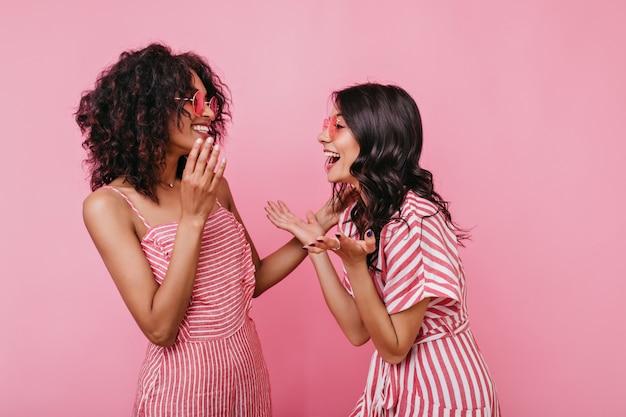 Una storia divertente ha fatto ridere di cuore due amici. ritratto di ragazze in abiti a righe rosa che si divertono.