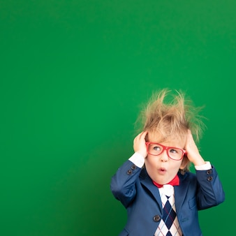 Funny stressed child student in class against green chalkboard.