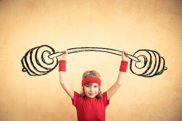 Funny strong child with drawn barbell. girl power and feminism concept. sport fitness kid