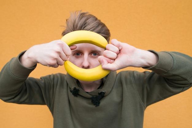 Смешной студент с бананами в руках на оранжевой стене