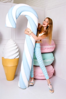 Ritratto divertente dello studio della donna abbastanza allegra che tiene il bastoncino di zucchero enorme gigantesco, amaretti grandi falsi e gelato su fondo, colori pastello.